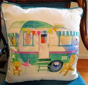 Pillow with colorful camper on it.