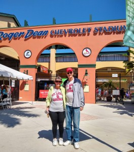 Betty and Dan standing in front of Roger Dean Stadium on a sunny day.