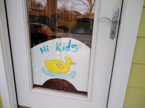 "Picture of a duck with ""Hi Kids"" on front door."