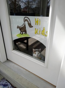 "Picture of a skunk with ""Hi Kids"" on a front door.   A calico cat is peering out underneath."