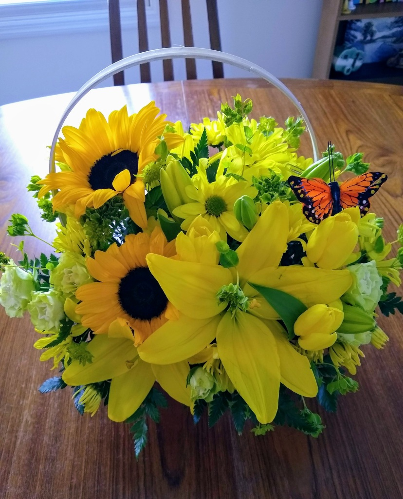 Large basket of yellow flowers.