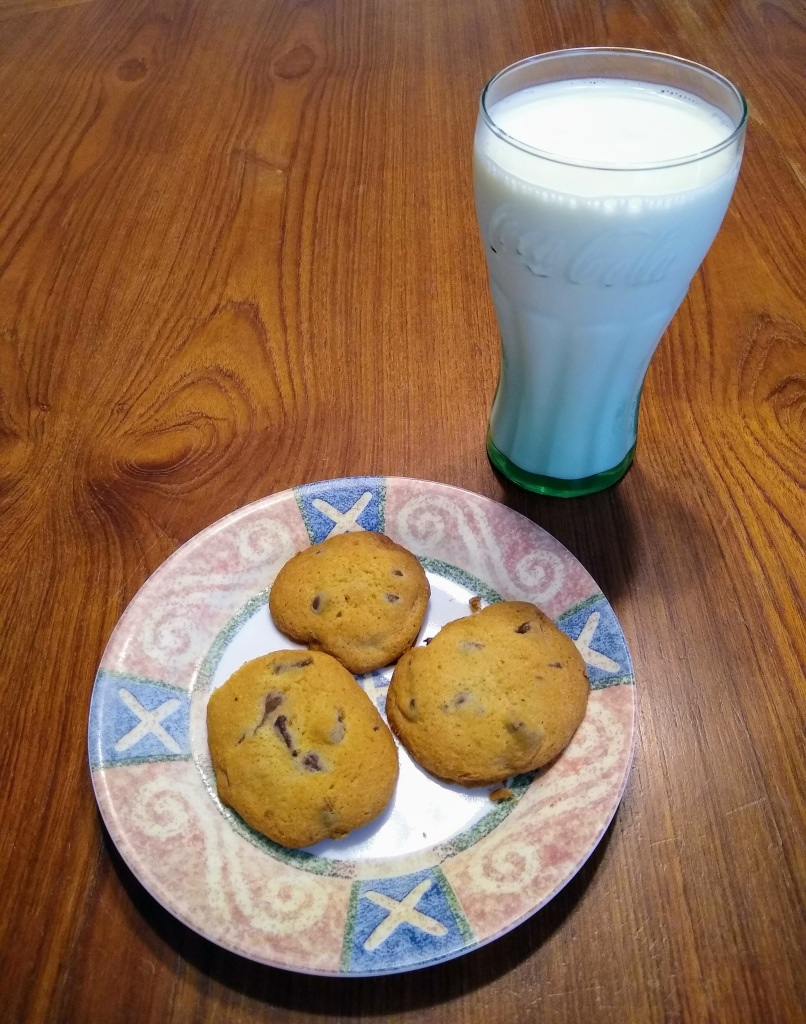 Glass of milk and plate of 3 chocolate chip cookies.