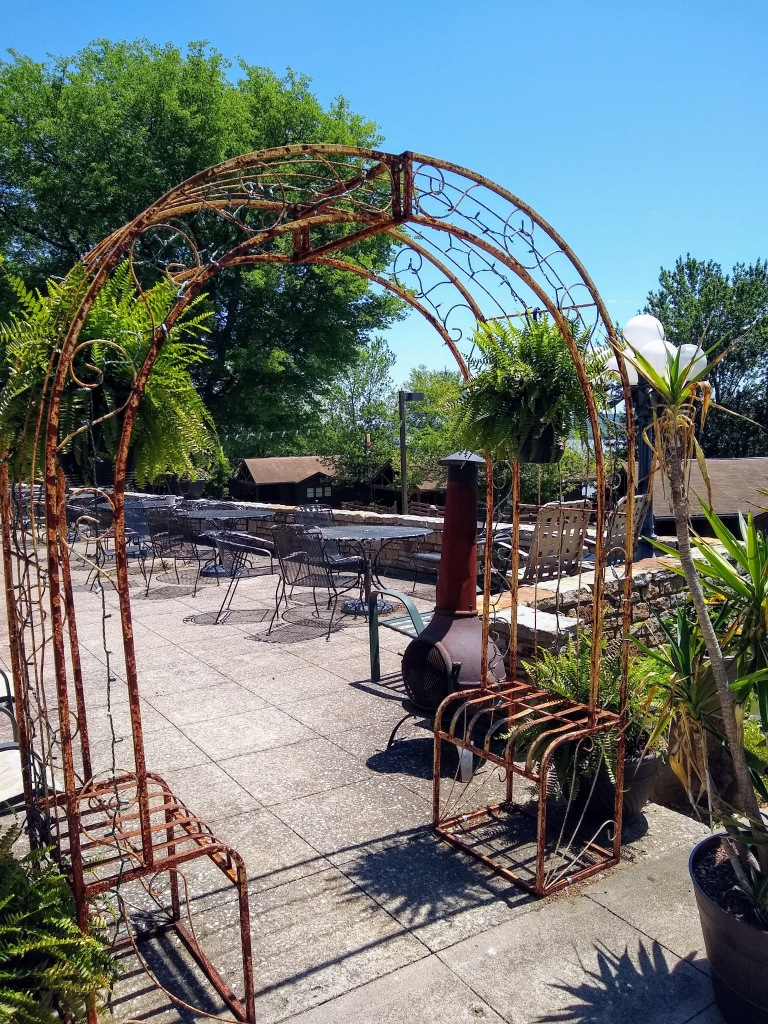 Metal arbor arch into restaurant patio overlooking the river.