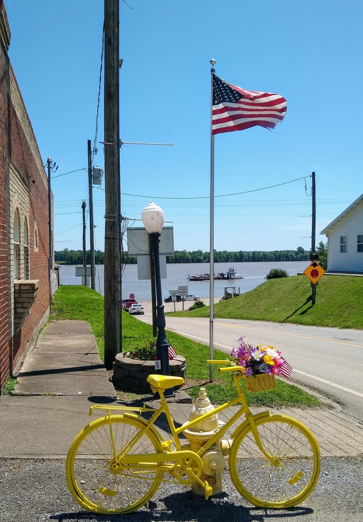 Yellow bicycle with American flag in background.
