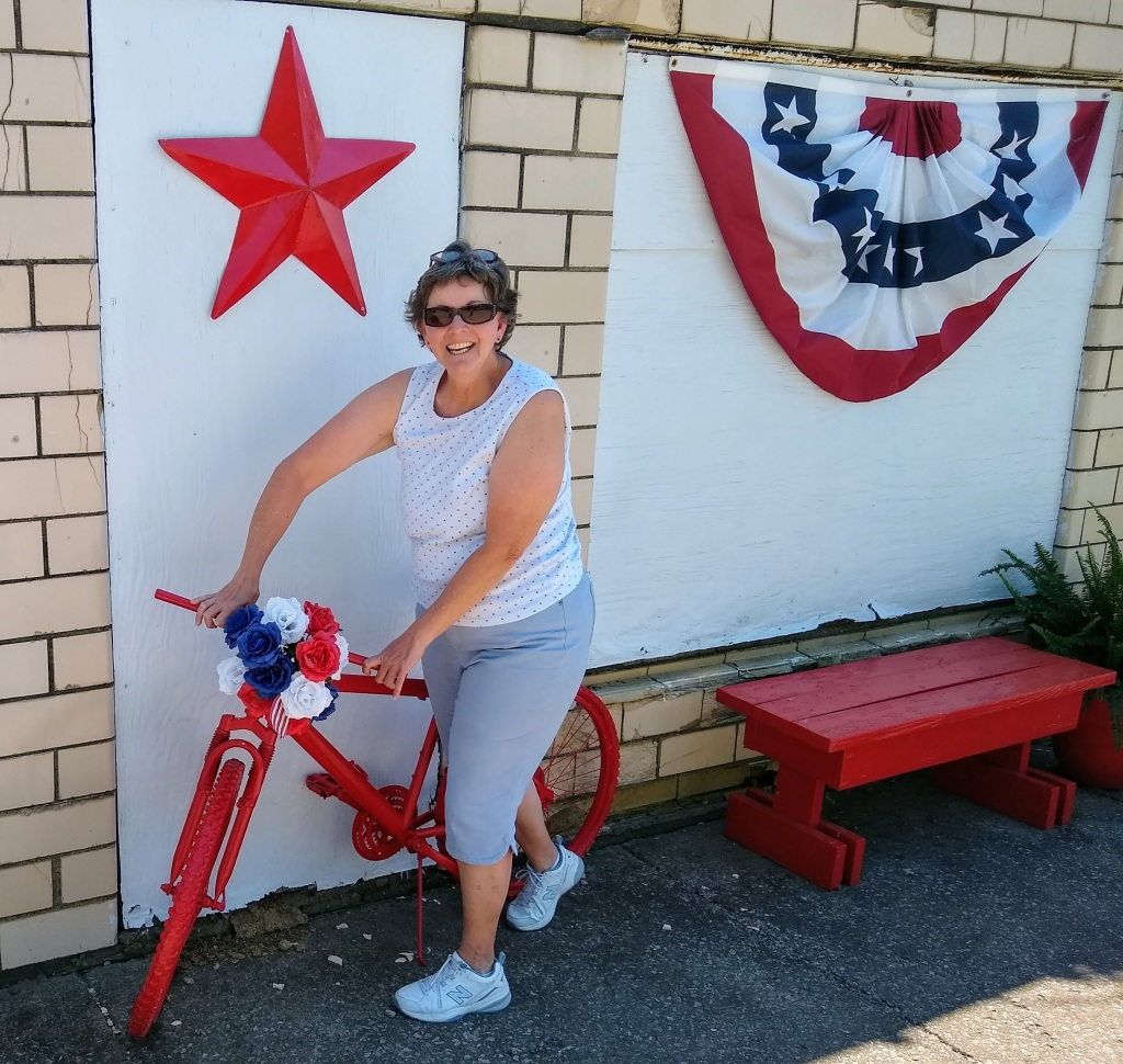 Betty with red bike and patriotic banner.