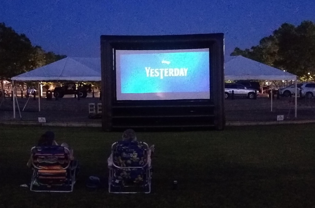 "Outdoor movie screen with ""Yesterday"" title screen."