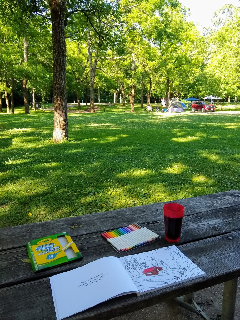 Picnic bench with coloring book on it.