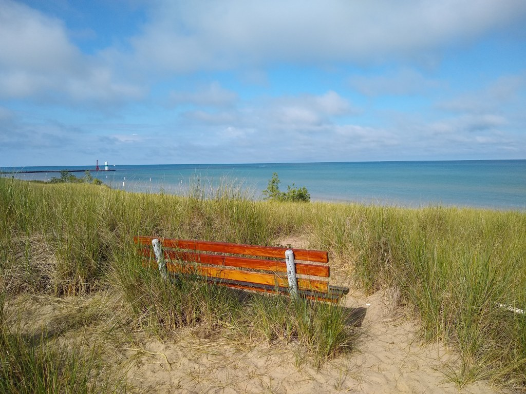 Bench on top of sand dune with view of Lake Michigan.