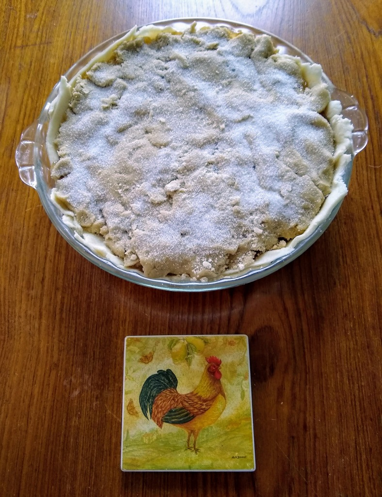 Pie ready to bake with rooster coaster under it.