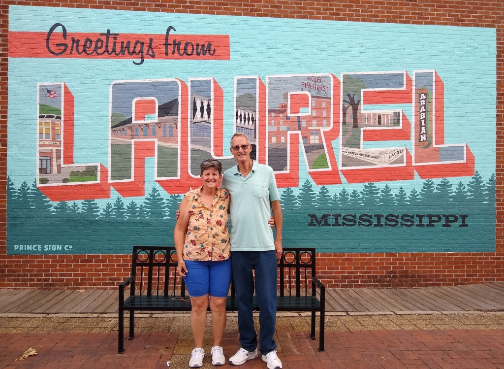 "Betty and Dan in front of ""Greetings from Laurel"" painted mural on brick wall."