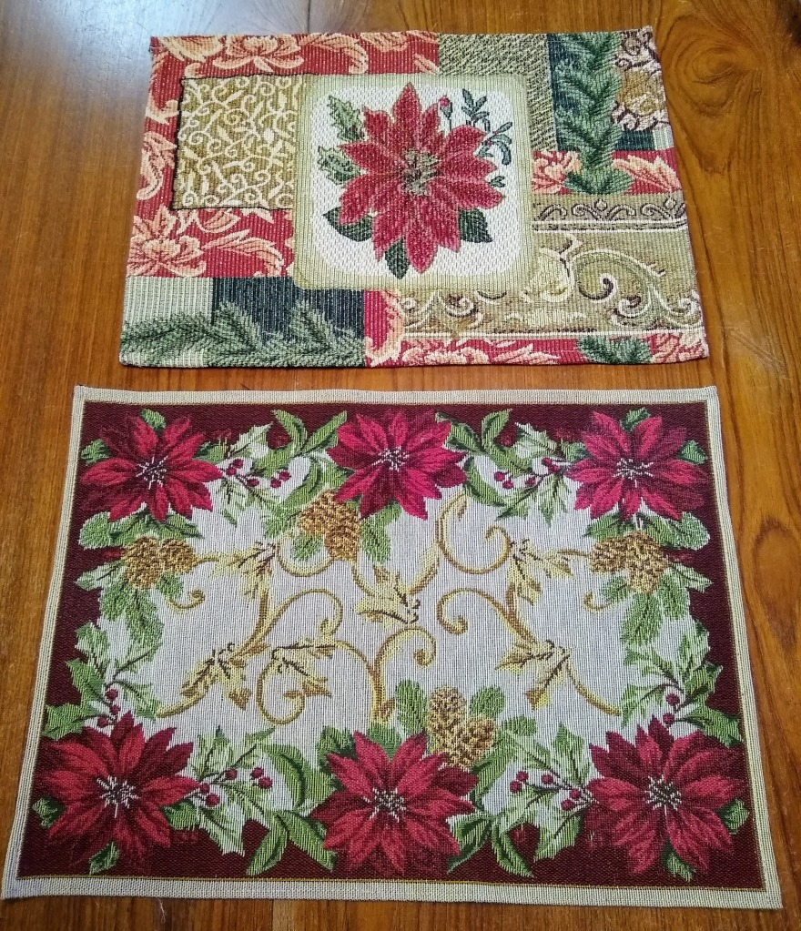 Two placements on the table.  One is the poinsettia, and one is a design with six smaller poinsettias and some gold scrolls in the middle.