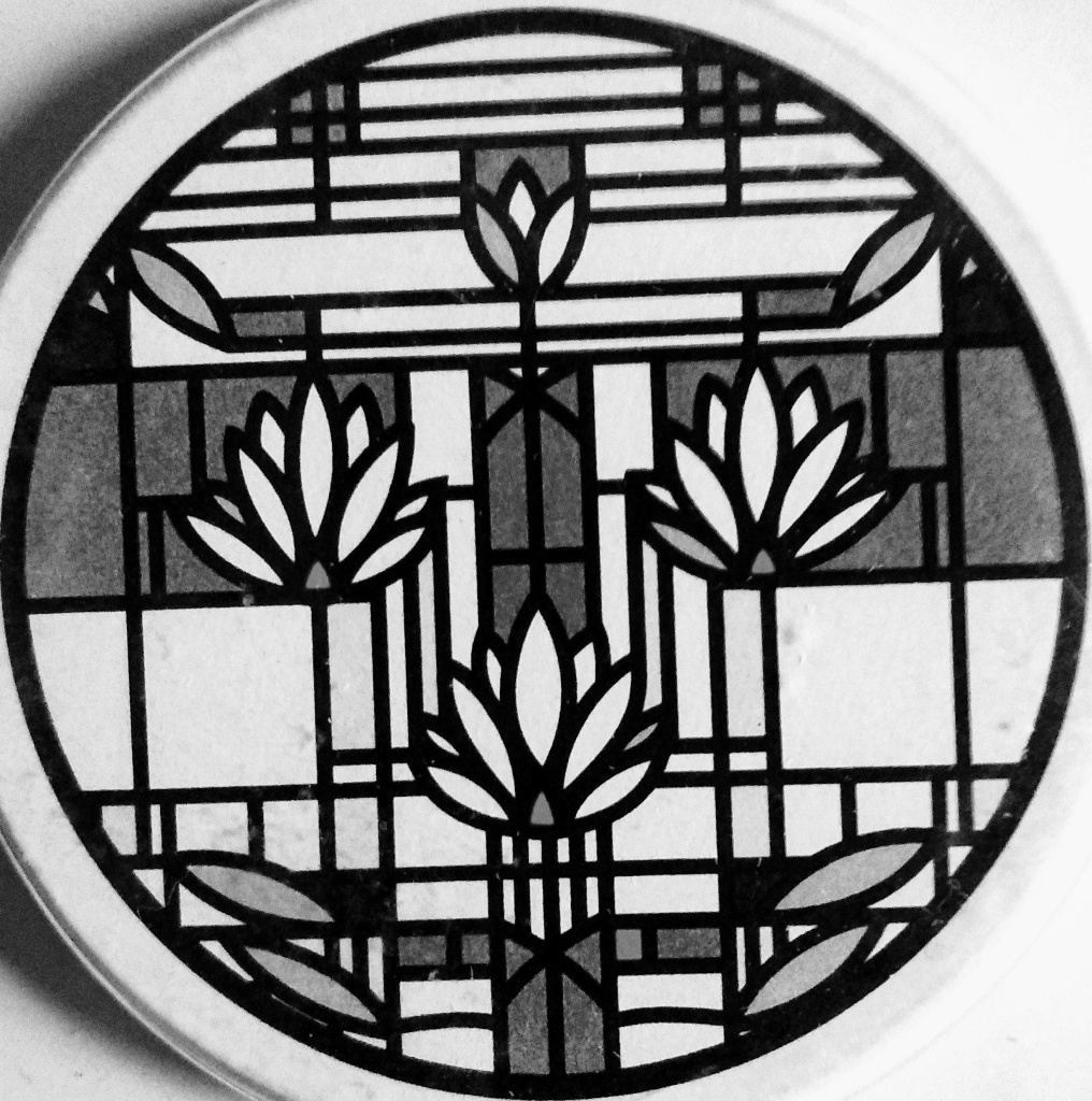 A black and white circle with a Frank Lloyd Wright floral design.