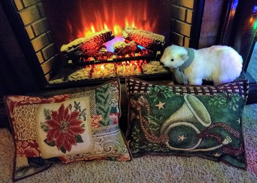 Two Christmas pillows in front of fireplace.  One pillow has a poinsettia, and one has a french horn.