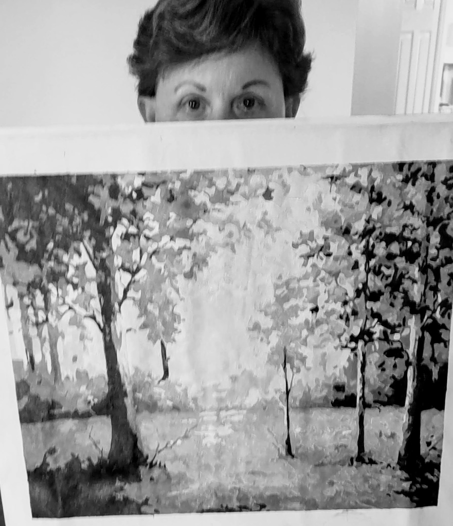 Black and white of Betty (from the eyes up) holding the paint by number canvas.