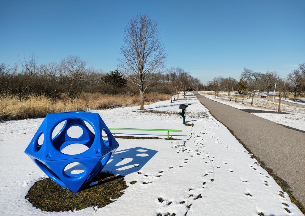 Walking path with snow on ground. Large blue geometric shape for climbing.