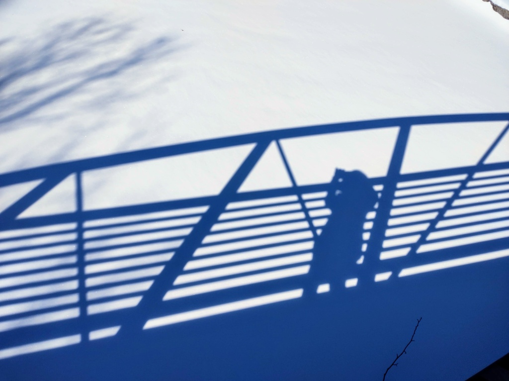 Shadow of bridge with a person taking a picture