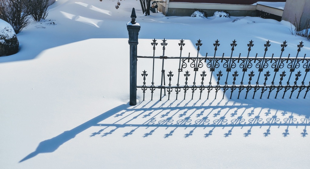 Wrought iron fence casting shadow on snow