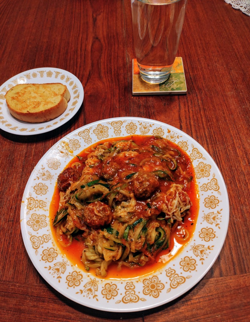 Dinner plate with meatball zoodles casserole, garlic toast and a glass of water.