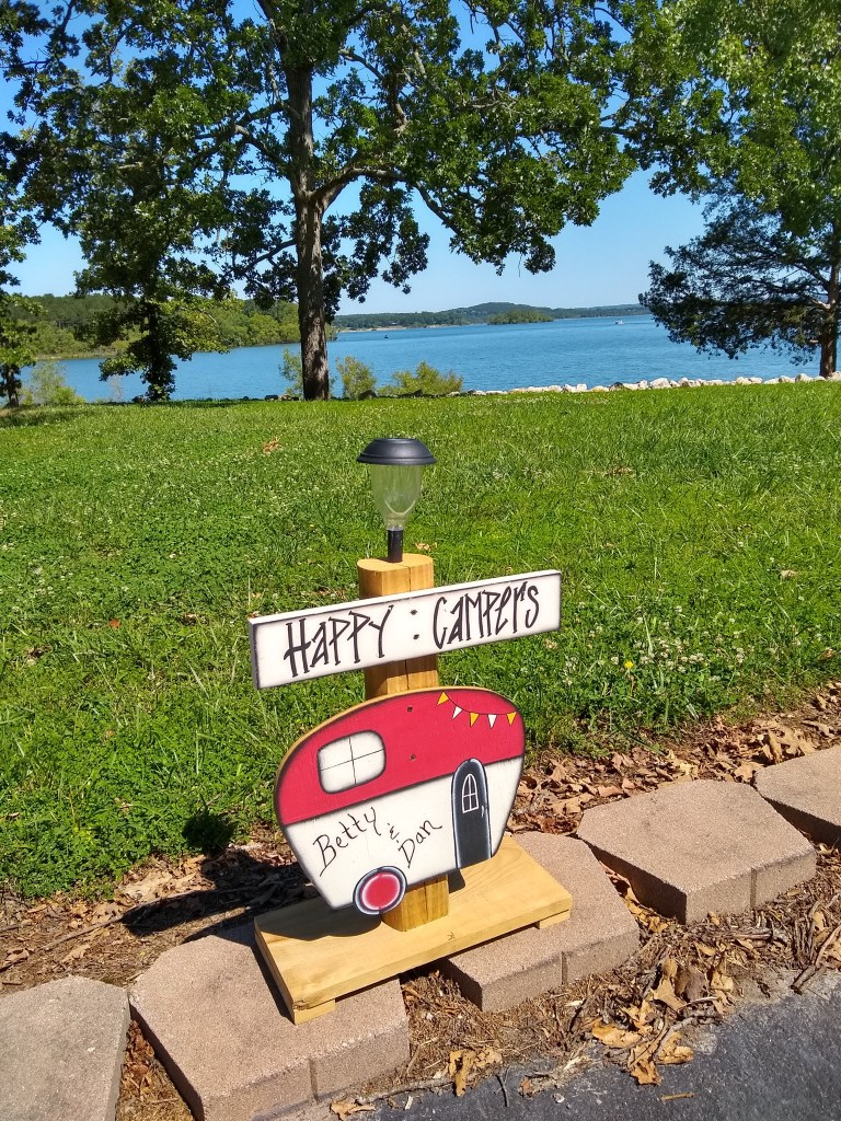 Happy Campers sign with lake in the background.