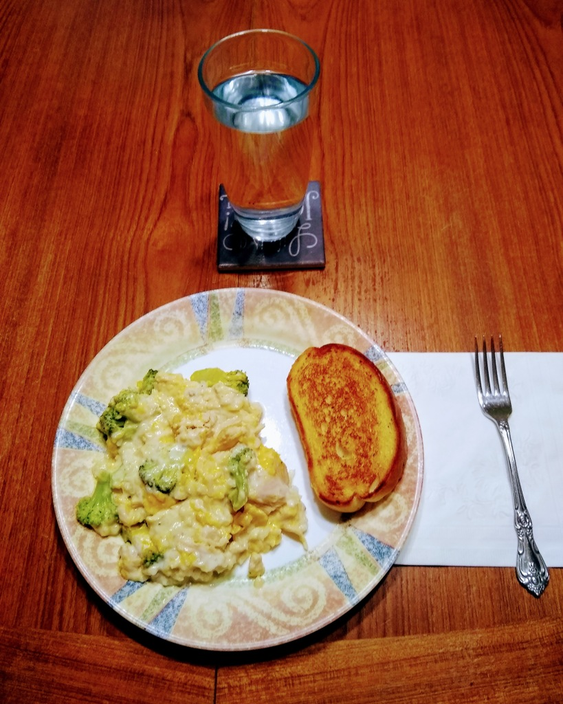 Dinner plate with casserole serving and a piece of garlic toast. Glass of water.