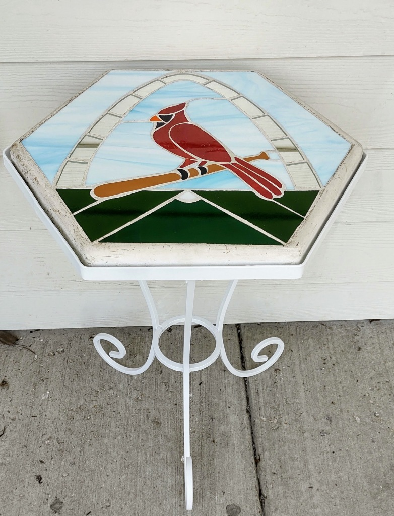 Repainted metal stand with stained glass stepping stone in it - i.e. a little patio table.
