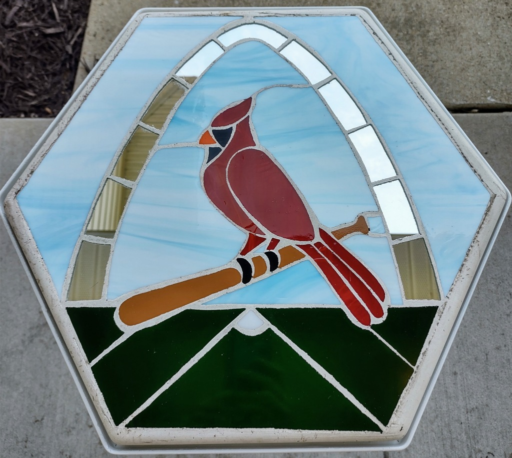 Stained glass stepping stone with a St. Louis Cardinal bird on the bat .  The St. Louis Arch is in the background. There is a ball field on the bottom of the stone.