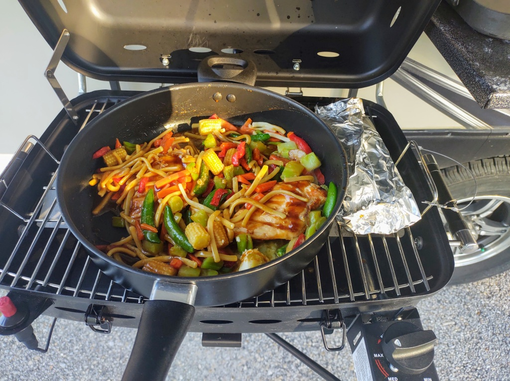 Teriyaki stir fry cooking in pan on the grill.