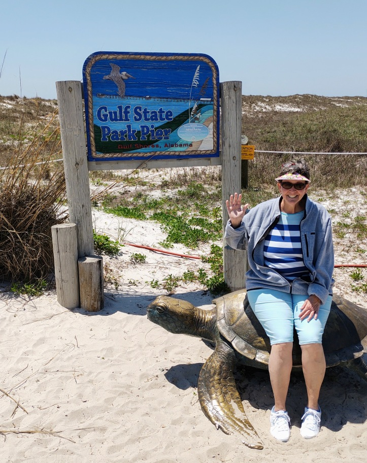 """Betty sitting on a bronze turtle with """"Gulf State Park Pier"""" sign in the background."""