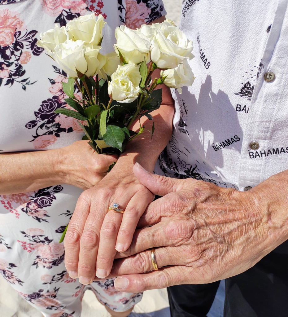 White roses with a woman and man's hands wearing wedding rings.