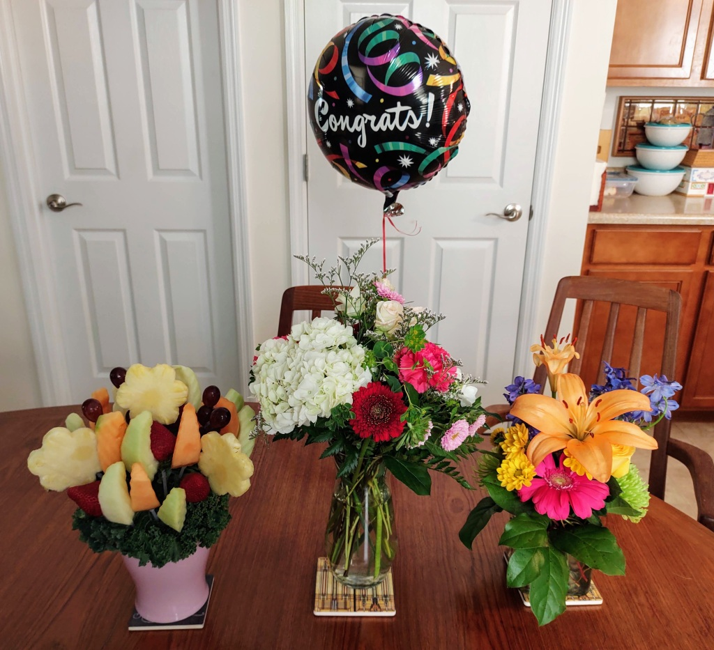 Three bouquets of flowers with a Congrats! balloon.