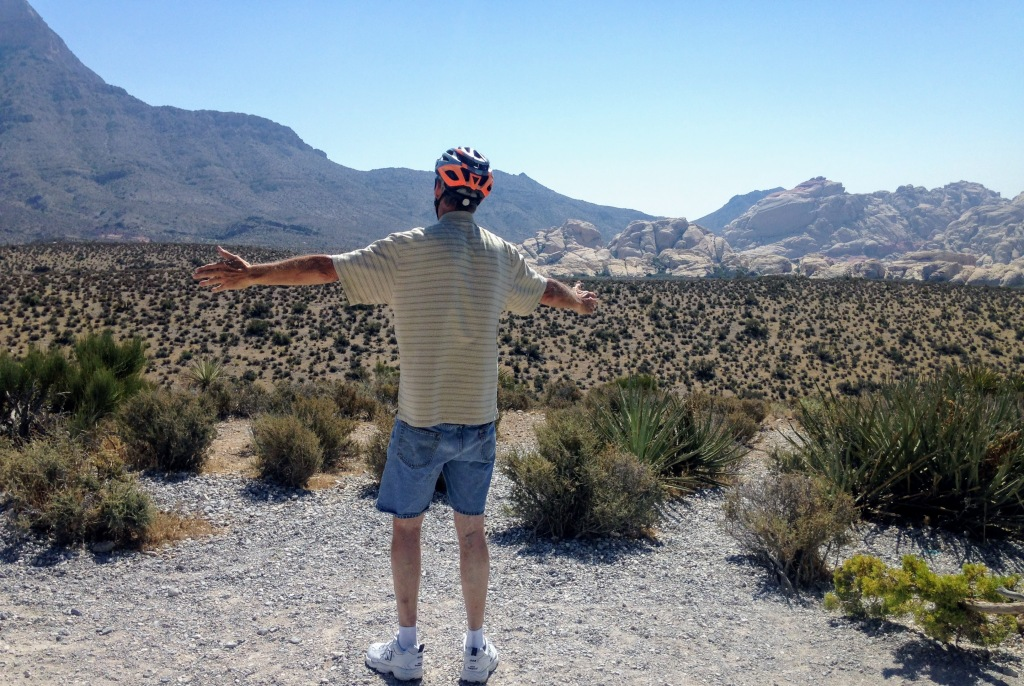Dan looking at mountains at Red Rock Canyon in Las Vegas with arms stretched out.