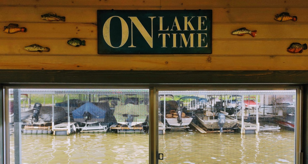 """View out a window of a line of boats at a marina.  The sign above says """"On Lake Time."""""""