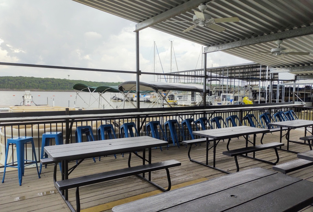 Outdoor eating area with picnic tables and view of the marina at The Galley restaurant.