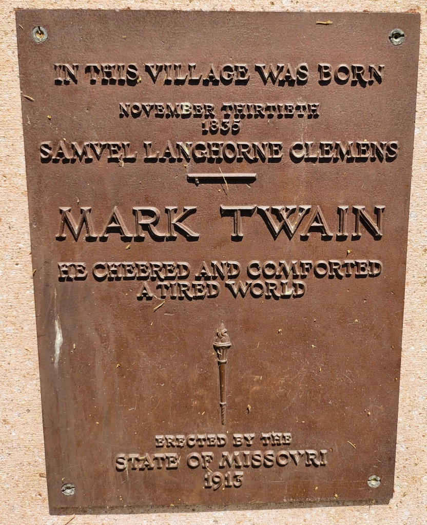 """Brass plate on marker.  """"He Cheered and Comforted A Tired World."""""""