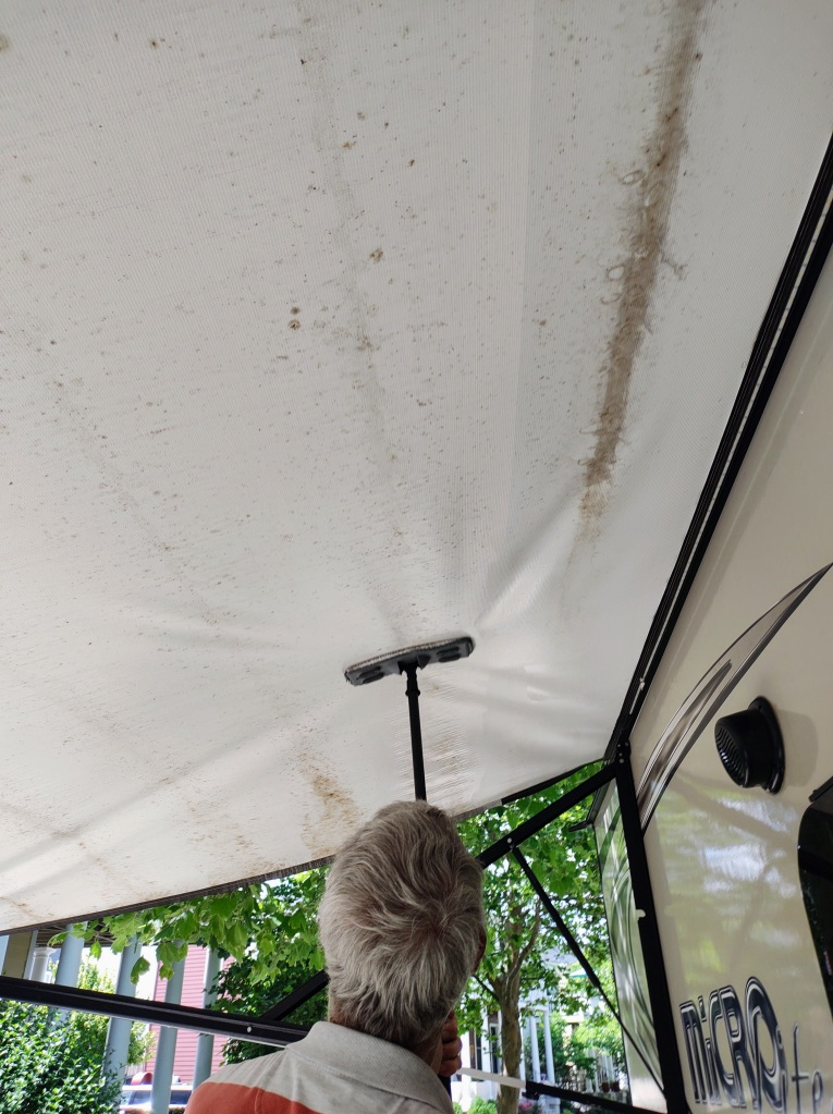 Close up of Dan cleaning the awning with a mop.