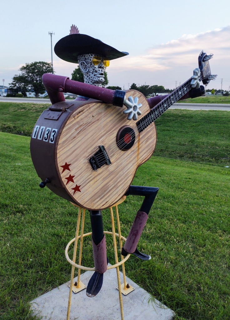 Mailbox which is a metal sculpture of a cowboy holding a guitar.