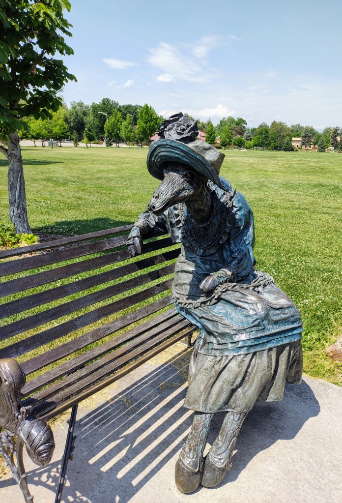 A bronze lady giraffe sculpture representing a fictitious character, Manilda G. Raffe.  She is sitting on a park bench.