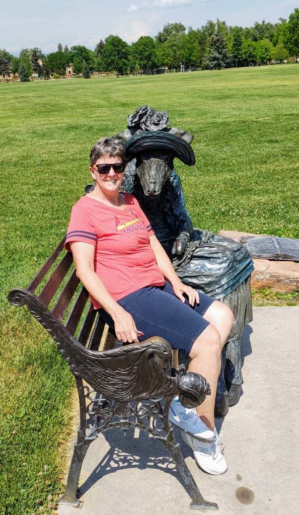 Betty sitting on a bench with a bronze sculpture of a lady giraffe.