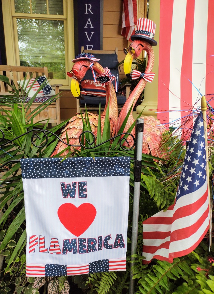 """Two flamingos wearing sunglasses wearing red, white and blue hats and ties/scarfs.  U.S. flag and a sign which says """"We love Flamerica."""""""
