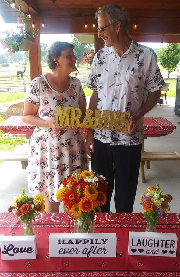 Betty and Dan holding a Mr&Mrs sign at Up North Market in Michigan.