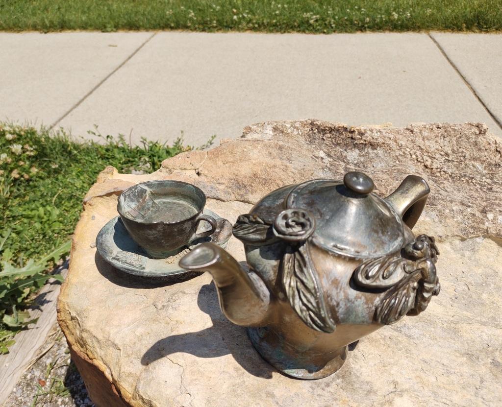 Bronze sculpture of a teapot and a teacup on a rock.
