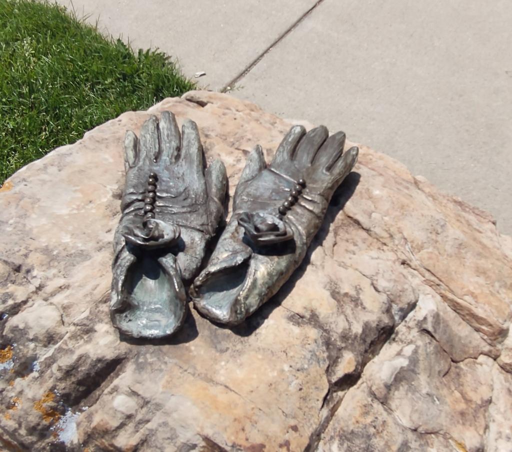 Bronze sculpture of gloves on a rock.