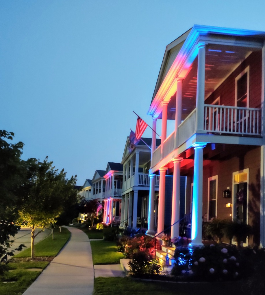 Evening picture of home lit up with red and blue and U.S. flag.