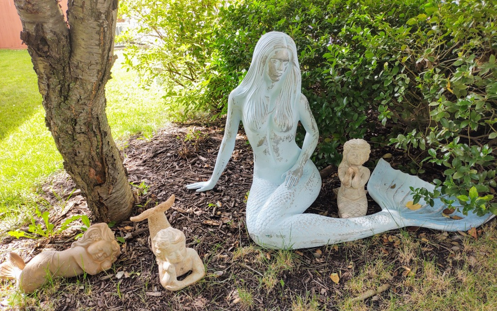 Blue mermaid statue in a front yard along with baby mermaid statues.