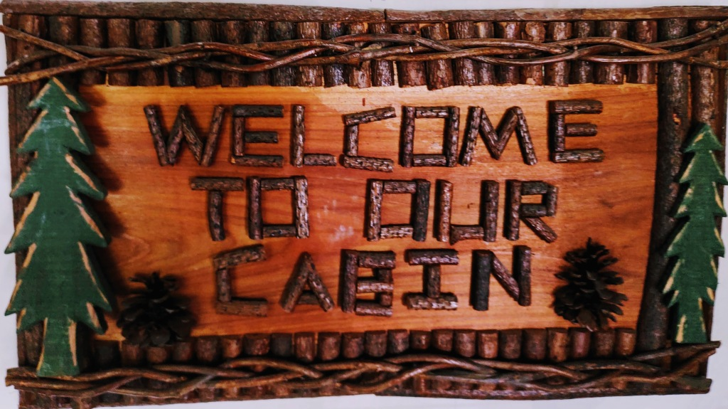 """""""Welcome To Our Cabin"""" sign."""