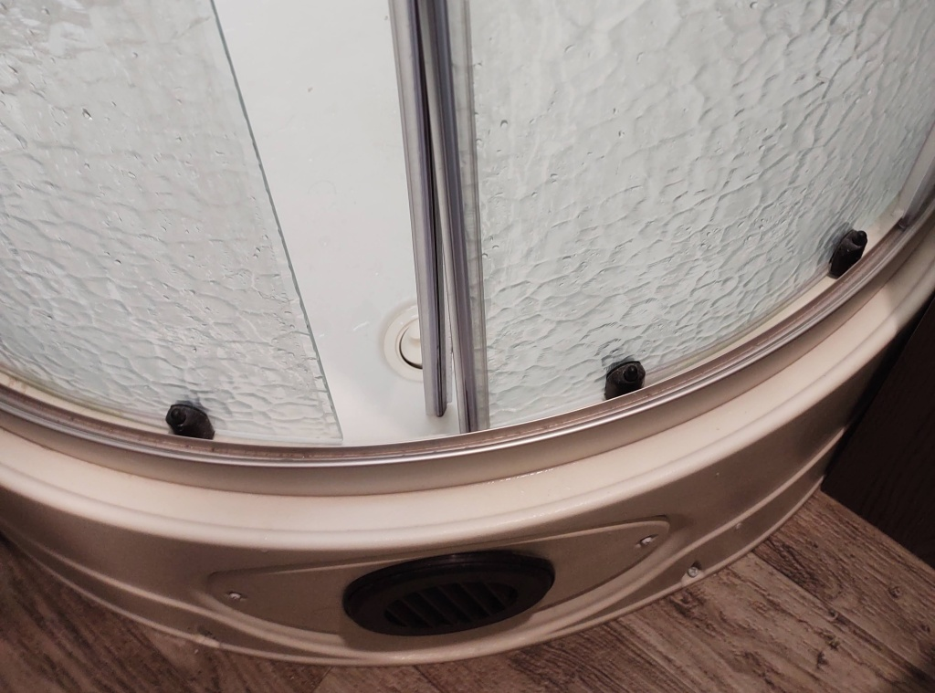 Shower doors with edging stuck on one side.