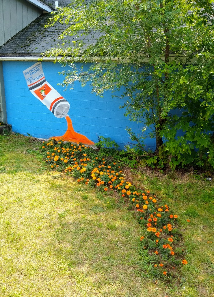 Painting on an outside wall of a tube of orange paint, in front of the wall and the tube is a line of orange marigolds.