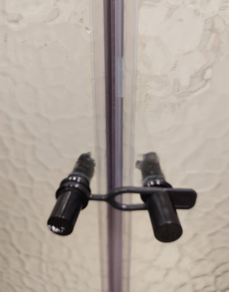 Shower doors closed.  If you look closely, you can see a dab of silicone about the handles.