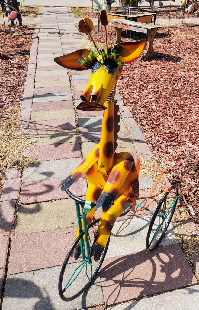 Giraffe riding a tricycle - metal art for sale.