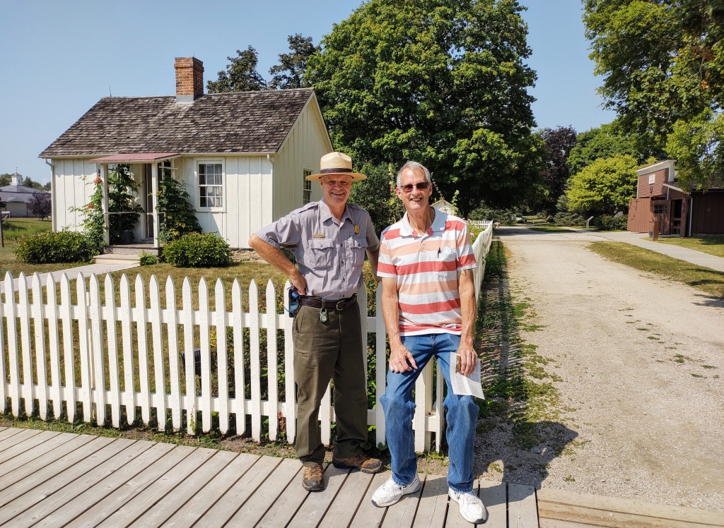 The ranger and Dan standing in front of the Birthplace Cottage.